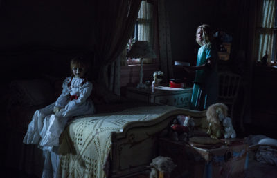 The Annabelle doll sits on a bed.