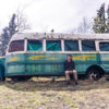 Anthony Ottati sits front of the bus once occupied by Christopher McCandless, now abandoned on Alaska's Stampede Trail