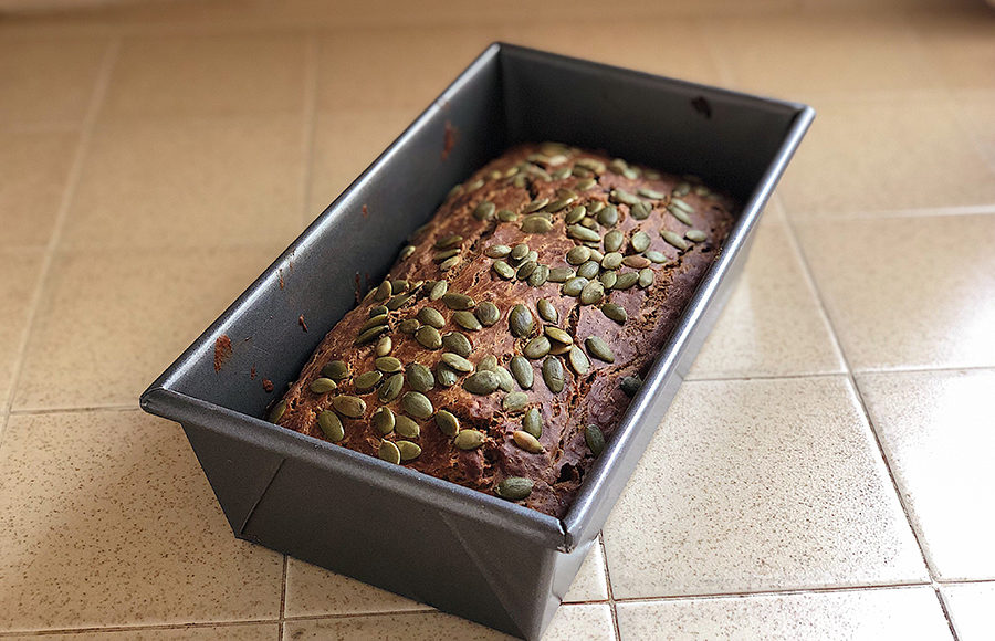 Freshly baked banana bread in a rectangular baking container rests upon tile covered countertop, coated in pumpkin seeds.