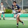 A Cal rugby player runs across the field with the ball.