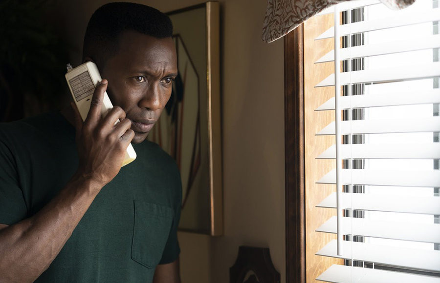 A man speaks on the phone and looks out of his window.