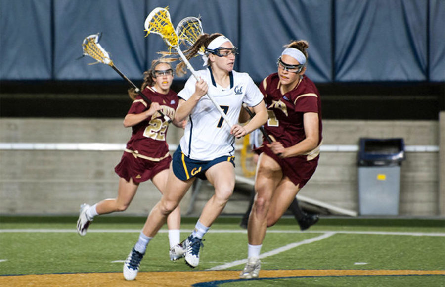 Three woman holding lacrosse sticks as they are running through a lacrosse field.