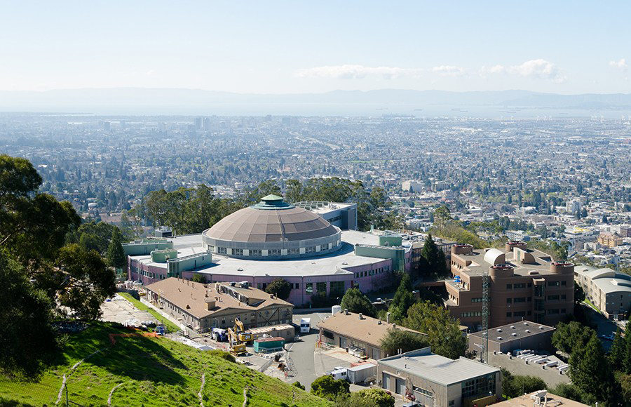 A view of a large building on top of a hill overlooking the East Bay.