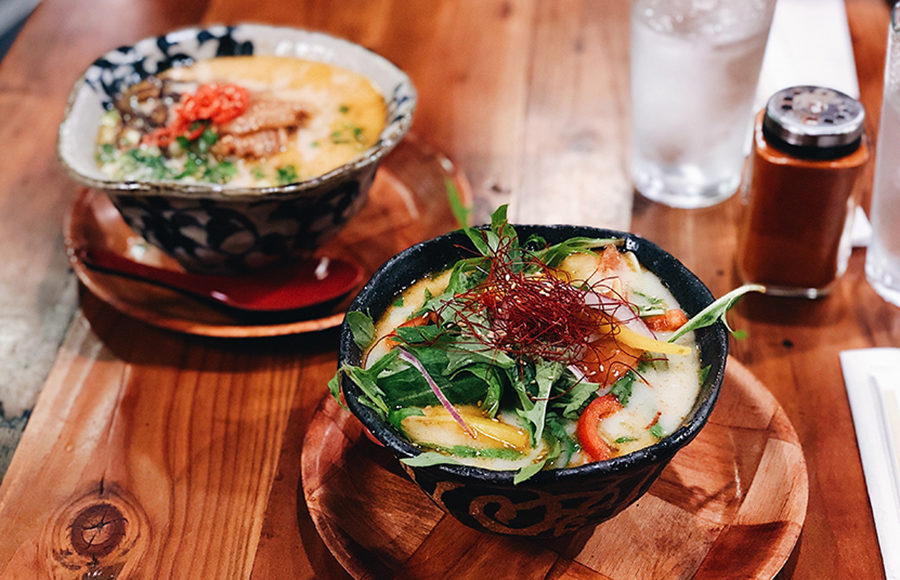 Two bowls of ramen on a wood table