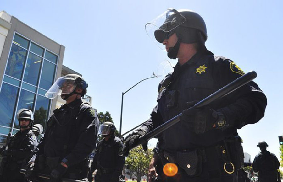 A police officer grasps a baton while standing next to other officers on the street.