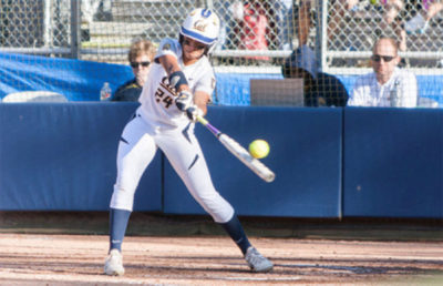 A softball player hits the ball with the ball.