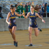Two track players run as they pass the baton from one to the other.