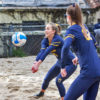 Volleyball player crouches down and prepares to bump ball.