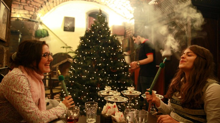 Syrian women smoke shisha as a waiter decorates the Christmas tree at a cafe in the old city of Damascus. The majority of the Christian community in Syria has decided to celebrate Christmas without decorations this year amid the ongoing Syrian conflict but the owner of the cafe decided to carry on with the tradition regardless. AFP Photo / Carole Alfarah