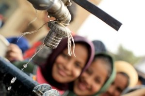 Egyptian girls stand in line at a water cistern to fill their containers with clean water at Al-Rahawe village