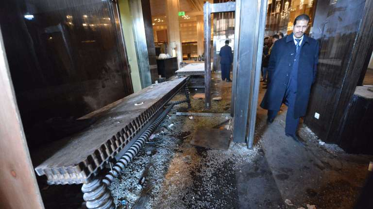 A man walks past the damage to the lobby of the Samir Amis Intercontinental Hotel after it was vandalized when protestors stormed the entrance last night, in central of Cairo on January 29, 2013. Egypt's military chief warned that the political crisis sweeping the country could lead to the collapse of the state, as thousands defied curfews and the death toll from days of rioting rose to 52. AFP PHOTO / KHALED DESOUKI