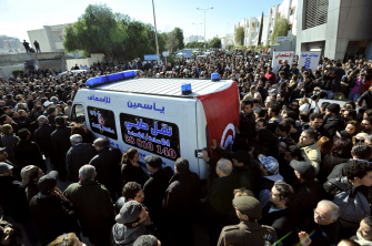 """People surround an ambulance transporting the body of Tunisian opposition leader and outspoken government critic Chokri Belaid, from from a clinic in Tunis to the public hospital for an autopsy, after he was shot dead with three bullets fired from close range, on February 6, 2013. Tunisian Premier Hamadi Jebali called the assassination """"an act of terrorism"""", as the country grapples with growing political instability. AFP PHOTO / FETHI BELAID"""