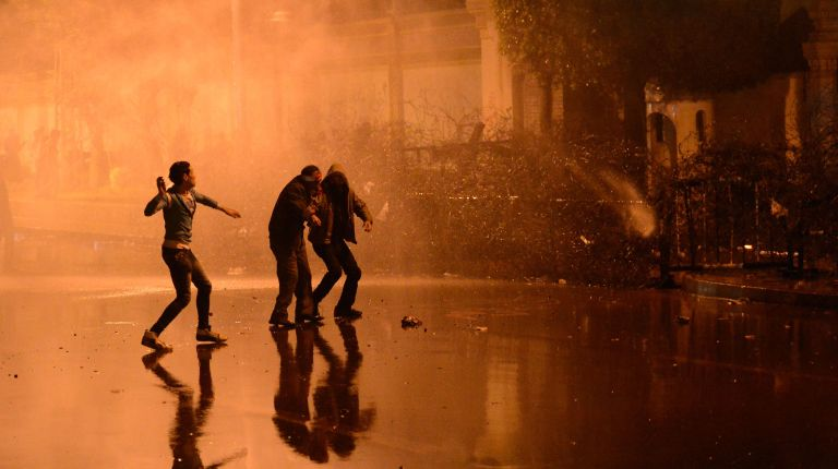Egyptian security use water cannon as protesters throw stones into the grounds of the presidential palace in Cairo, on February 11, 2013, as the opposition held rallies to mark the second anniversary of former president Hosni Mubarak's overthrow. AFP PHOTO / KHALED DESOUKI