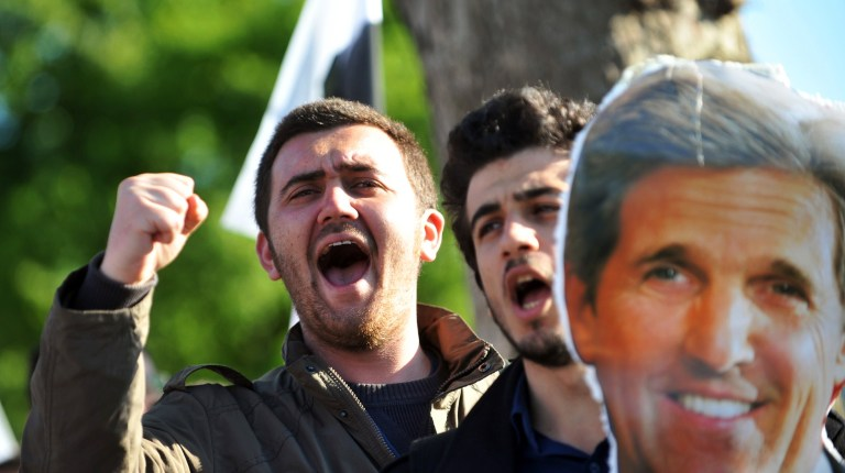 Turkish nationalist students chant slogans as they hold a picture of US Secretary of State John Kerry during a demonstration against his visit at the Friends of Syria meeting on April 20, 2013 in front the meeting area on Uskudar in Istanbul.(AFP Photo)