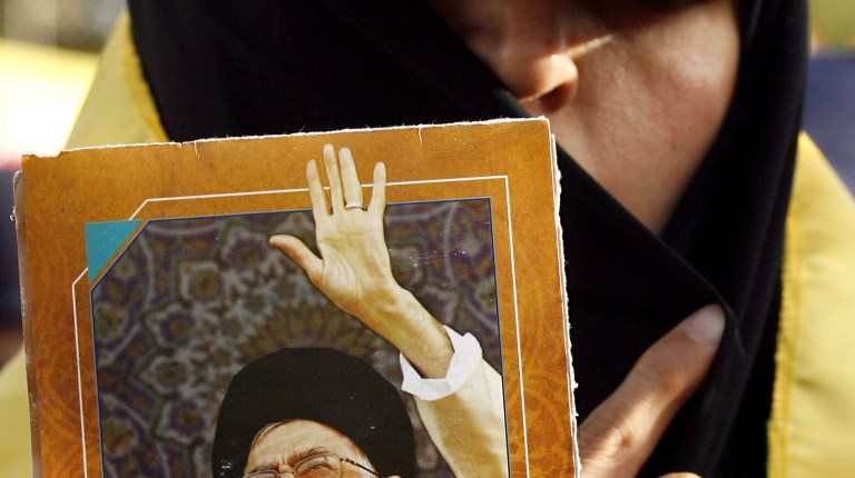 A Lebanese woman and supporter of Hezbollah holds a picture of Iran's supreme leader Ayatollah Ali Khamenei in Mashghara in the western Bekaa Valley on May 25, 2013 during a ceremony marking the 13th anniversary of Israel's military withdrawal from Lebanon. (AFP Photo)