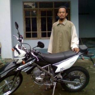 Ust.Gus Wahid sedang berdiri di depan motor yang merupakan hasil Wakaf dari para Wakif. (BWA)