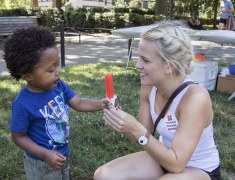 Intern Gracie Brumsickle hands popsicle to child
