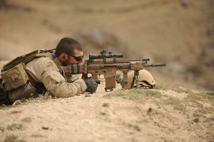 A U.S. Navy SEAL with a Mk. 17 SCAR  takes up a defensive position in a village in northern Zabul province, Afghanistan, April 10, 2010.   U.S. Navy photo by Chief Mass Communication Specialist Jeremy L. Wood