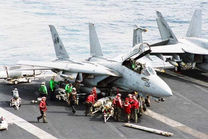 Sailors prepare an F-14D Tomcat aboard USS Abraham Lincoln (CVN 72) for a strike on Iraq during Operation Iraqi Freedom in 2003. U.S. Navy photo by Photographer's Mate 3rd Class Michael S. Kelly.