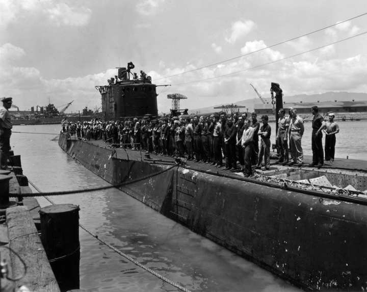 Marine Raiders and sailors crowd the deck of USS Argonaut as she is warped into the dock at Pearl Harbor after the Makin Island raid. National Archives photo