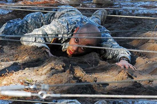 A soldier crawls through a present-day obstacle course