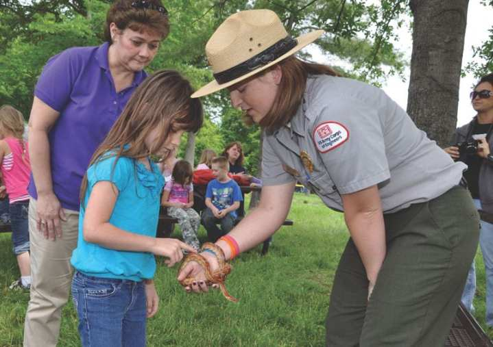 """Park ranger Alicia Cannon let Caneyville, Ky., first-graders touch turtles, non-venomous snakes, and ferrets during their visit to Louisville District's Rough River Lake May 19, 2011, for a mini eco-meet. One of the goals of President Barack Obama's America's Great Outdoors initiative is to """"build stewardship values and engage youth in conservation and recreation."""" U.S. Army Corps of Engineers photos"""