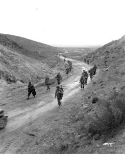 U.S. Army soldiers from the 2nd Battalion, 16th Infantry Regiment march through the Kasserine Pass and on to Kasserine and Farriana, Tunisia, Feb. 26, 1943. After Maj. Gen. Ernest N. Harmon stabilized the front the U.S. Army pushed on. U.S. Army photo