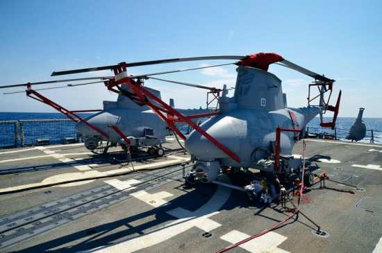Two of the four Fire Scouts embarked on USS Klakring (FFG 42) prepare for deployment in June 2012. With a record number of unmanned helicopters aboard Klakring, Fire Scout regularly maintained 12-hour days on station, regularly switching aircraft to provide continuous and thorough support. U.S. Navy photo by Erik Hildebrandt