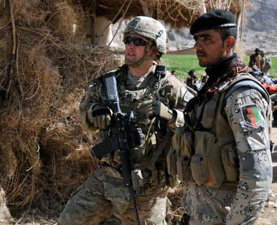 """Capt. Derek C. Knapp, with Security Force Assistance Team 10, Texas Army National Guard, and his Afghan Border Police counterpart, discuss security near the area known as the """"Jungle"""" during Operation Southern Fist III, March 5, 2013, in Kandahar province, Afghanistan. If the U.S. turns inward after over a decade of continuous war a """"Stalled Engine"""" scenario is likely. U.S. Army photo"""