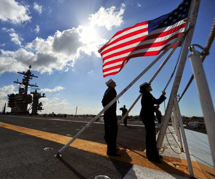 U.S. Navy Aviation Boatswain's Mates (Handling) 3rd Class Joe Montez, left, and Elizabeth Mongkhonvilay shift the colors aboard the aircraft carrier USS Carl Vinson (CVN 70) Feb. 11, 2013, as the ship transits San Diego Bay. What role the U.S. chooses to play in the coming years will be of vital importance. U.S. Navy photo by Mass Communication Specialist 3rd Class George M. Bell