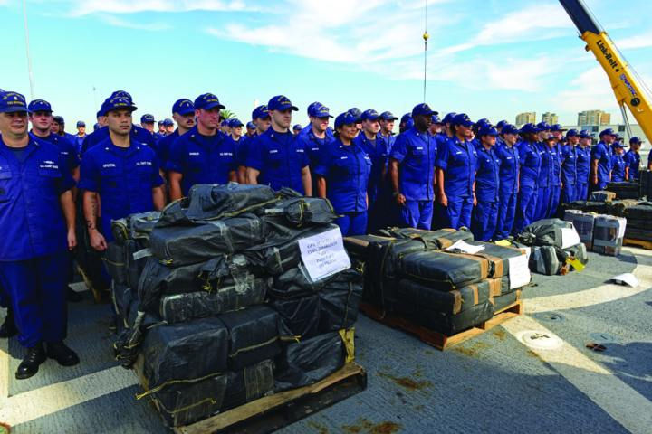 The crew of the CGC Boutwell stands at attention among pallets of seized cocaine during an award ceremony aboard their cutter at Naval Base San Diego, Oct. 6, 2014. The Boutwell returned from a 90-day joint and combined forces counter-drug patrol in which it made six different drug interdictions as part of Operation Martillo. U.S. Coast Guard photo by Petty Officer 2nd Class Connie Terrell