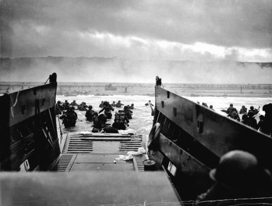 A Coast Guard-manned LCVP from the USS Samuel Chase disembarks troops on the morning of June 6, 1944, at Omaha Beach. Official U.S. Coast Guard photograph