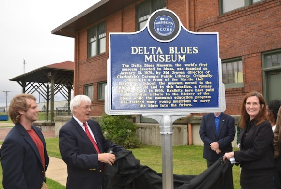 Shelley Ritter (right), director of the Delta Blues Museum, and Bill Gresham (left) president of the museum board of trustees official unveil the Mississippi Blues Trail Marker. Allison Washington of Jackson, Music Trails program manager with the Mississippi Development Authority, said the marker was the 13th unveiled  in Clarksdale and Coahoma County. Photo by Panny Mayfield