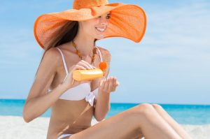 Happy Young Woman At Beach With Orange Hat Applying Suntan Lotion