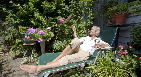 Senior woman with wineglass relaxing on lounge chair in garden