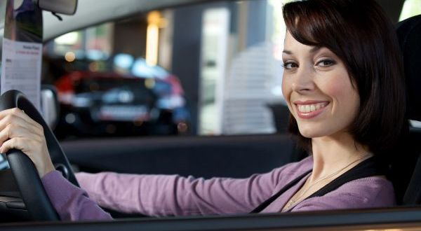 Portrait of young woman sitting in driver's seat at car dealersh