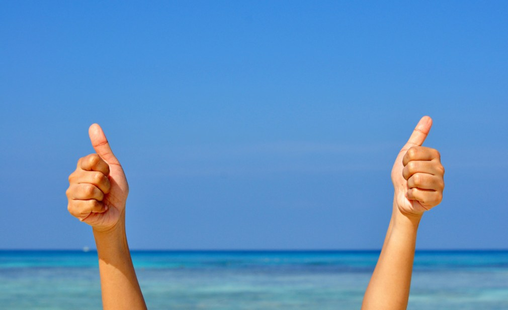 Two hand making the sign of Like with the blue sea and sky background