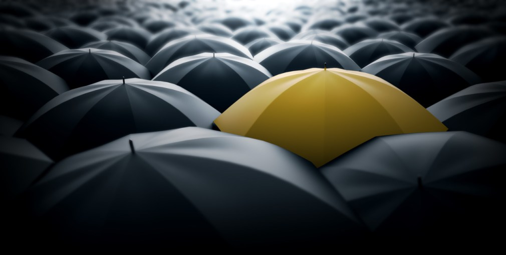 Yellow umbrella in the middle of a sea of black umbrellas, representing special element, a different view in the society.