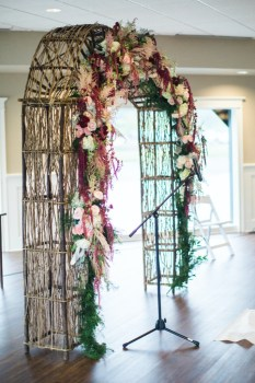 wedding ceremony arch in green, deep red, white and pink