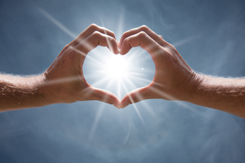 Hands in a heart shape with a sunflare shooting through on a blue sky.