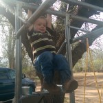 Nolan attempting the monkey bars
