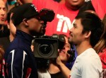 LAS VEGAS, NV - MAY 01: Floyd Mayweather Jr. (L) and Manny Pacquiao face off during their official weigh-in on May 1, 2015 at MGM Grand Garden Arena in Las Vegas, Nevada. The two will face each other in a welterweight unification bout on May 2, 2015 in Las Vegas.   Jamie Squire/Getty Images/AFP