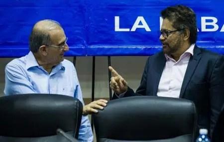 El jefe de la delegación de las FARC Iván Márquez (d) habla con el jefe de la delegación del gobierno colombiano Humberto de la Calle (i) en rueda de prensa en el Palacio de las Convenciones de La Habana el 19 de enero de 2016. AFP / YAMIL LAGE