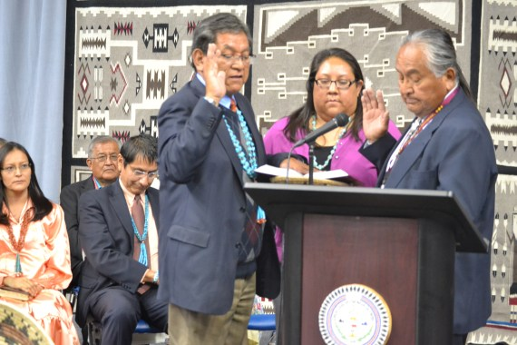 "Navajo Nation President-elect Russell Begaye takes the oath of office, as his daughter, Karis Begaye, stands by him. Navajo Nation Supreme Court Chief Justice Herb Yazzie gives the oath at noon in the ""Fighting Scouts"" Events Center in Fort Defiance, Ariz., May 12, 2017. Photo by Marley Shebala"