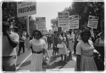A procession of African Americans carrying signs for equal rights, integrated schools, decent housing, and an end to bias at the March on Washington on Aug. 28, 1963. Photo by Warren K. Leffler (Library of Congress)