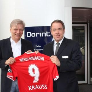 SVWW-Geschäftsführer Georg Kleinekathöfer überreicht Jörg Krauß (rechts), dem Hoteldirektor des Dorint Pallas Wiesbaden, ein Trikot des Drittligisten mit der Nummer 9. Die Zusammenarbeit ist damit symbolisch besiegelt. Foto: SVWW/Abdruck honorarfrei