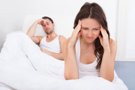 Frustrated Woman Sitting On Bed In Front Of Young Man