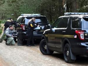 Police officers take cover behind vehicles lining the road during a standoff at a rural property near Belfair, Washington, February 26, 2016 in this handout photo provided by Mason County Sheriff's Office in Shelton, Washington. REUTERS/Mason County Sheriff's Office/Handout via Reuters