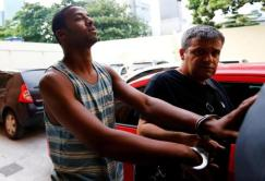 Rai de Souza (L), 22, suspected of being involved in the gang rape of a teenage girl, with a video of the assault circulated widely on social media, is escorted at the Police Station for crimes against minors in Rio de Janeiro, Brazil, May 30, 2016. REUTERS/Ricardo Moraes