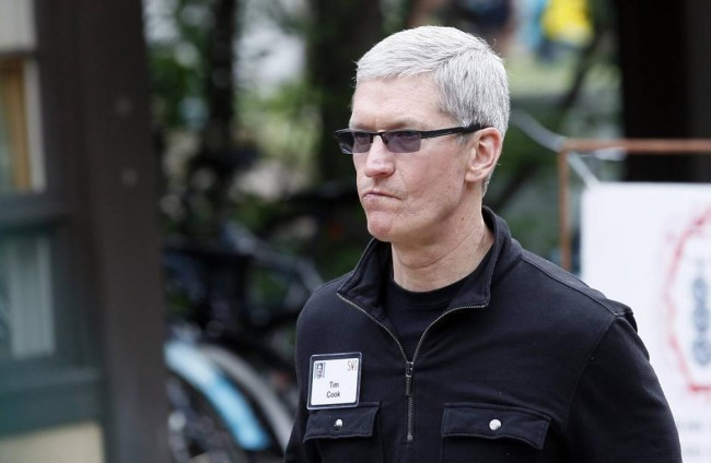 Tim Cook, Apple CEO walks past a news conference being held by Eric Schmidt, executive chairman of Google at the annual Allen and Co. conference in Sun Valley